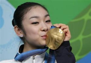 South Korea's Kim Yu-Na kisses the gold medal she won in the women's figure skating event at a news conference during the Vancouver 2010 Winter Olympics